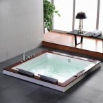 wide hot-bathtub built-in for indoor with water tap feature luxurious grey vinyl floor laminated-wood floor black table for putting bathing properties elegant table lamp in black tone