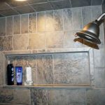 wide subway tiles built-in shelf for storing bath supplies a planted showerhead