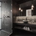 wonderful black bathroom concept with ravishing stone walling with energizing white lighting and transparent glass shower in concrete flooring