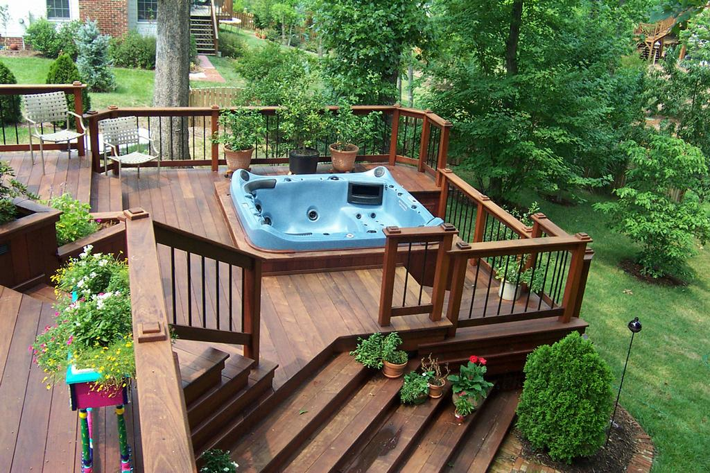 wood home patio with a large hot tub some pieces of patio furniture and beautiful decorative