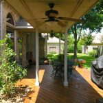 big ceiling fan with lamp in the center for porch a set of furniture for patio or porch wood planks floor for porch