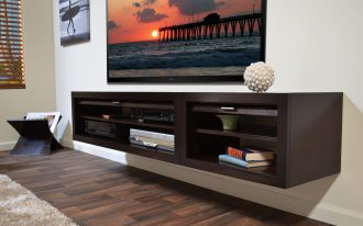 black-wood floating media desk with multiple shelves a big flat TV a decorative ball  darkwood floors light brown fury carpet an artistic painting as wall decoration electric appliances on shelves