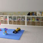 blue carpet blocks with some kids' play lateral shelving unit with many kids' stuffs