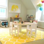 bright yellow carpet with white patterns a set of wood furniture for study a cute yellow elephant painting on wall a cute laundry box a wood study desk