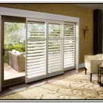built-in white shutter window treatment for sliding glass door a white arm chair with side-table in star shape warm and soft brown carpet with flower patterns rattan furniture for porch beautiful wallpaper