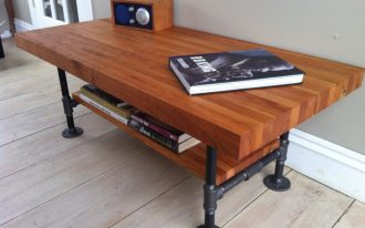 butcher block table with unique legs and under bookcase a audio system and book on table top