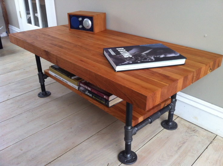 butcher block table with unique legs and under bookcase a audio system and  book on table - Butcher Block Coffee Table: Unique Focal Point For A Living Room