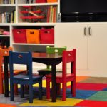 colorful square-patterns carpet colorful chairs with black table for kids a white book shelf with many books collections and colorful basket for storage a white TV console with cabinet