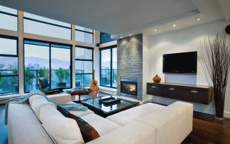 cozy and classy living room with white living room furniture  a minimalist floating wood TV stand and an electric fireplace mantel a huge glasss vase with dried-root as an ornament