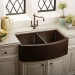 double farm sinks made from darker copper with classic copper faucet topless water jug and a plate of raw and fresh vegetables two small pots with decorative plants a pile of flat mini plates