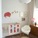 ethnic patterns carpet a white nurturing chair a wood buffet furniture under glass window  elegant white pendant lamp a baby box furniture a red bear painting with no frame