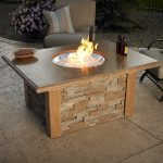Fire Table With Wood Top A Pair Of Cozy Outdoor Chairs Two Bottles Of Drinks