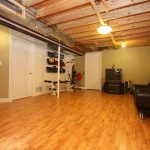 floor basement wood covering a black sofa with pillows a black TV console a big audio system
