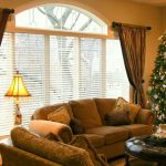large arched window with white shutter and gold curtains as window treatments a big Christmas tree with beautiful decoration comfy sofas set with round black-leather coat table