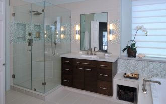 luxurious bathroom remodel idea with glass shower room with some built-in shelves  minimalist wood vanity with white marble countertop and sink plus faucet frameless mirror with wall-lighting