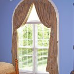 minimalist white shutter and curtain window treatments for an arched window