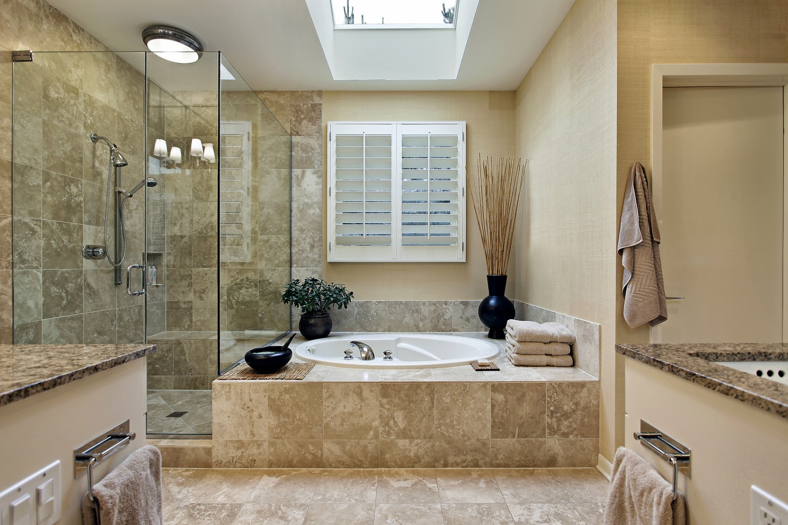 modern bathroom design with round white tub frameless glass door shower space modern bathroom appliances  brown marble tiles for shower wall and bathroom floors a pile of white towels black decorative vases