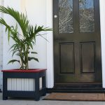 outdoor mini black tree planter box that is placed in outdoor door way