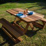 picnic table made with chairs made from wood planks material two glasses of fresh drinking and a pair of dishware