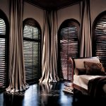 pretty dramatic look of room with several arched windows dark shutter window treatment dark grey floor to ceiling curtains for windows treatments a settee furniture with pillows