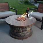 Round Fire Table With Wood Surface And Natural Stone Leg Two Glasses For Wine A Wine Bottle Two Units Of Wood Chairs With Comfy Seating Feature