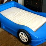 Simple Nice Awesome Cute Tiny Race Car Bed For Toddler With Blue Plastic Made Concept Design With Imitated Wheels Design
