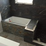 small and simple bathroom re-design with built-in concrete water container river rocks floor idea for wet area
