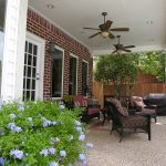twin ceiling fan units in the porch luxurious outdoor furniture for the porch red bricks wall system brown Epoxy painted floors