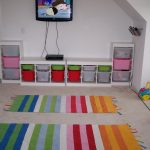 two pieces of rainbow-colors carpets TV console with shelves containing colorful plastic container as the storage units some kids' stuffs a TV set