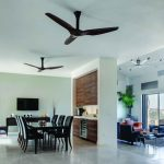 two units of black ceiling fans a set of dining furniture in black a credenza furniture as media console  TV screen plant ornaments on artistic pots a ceiling fan with multiple blades in living r