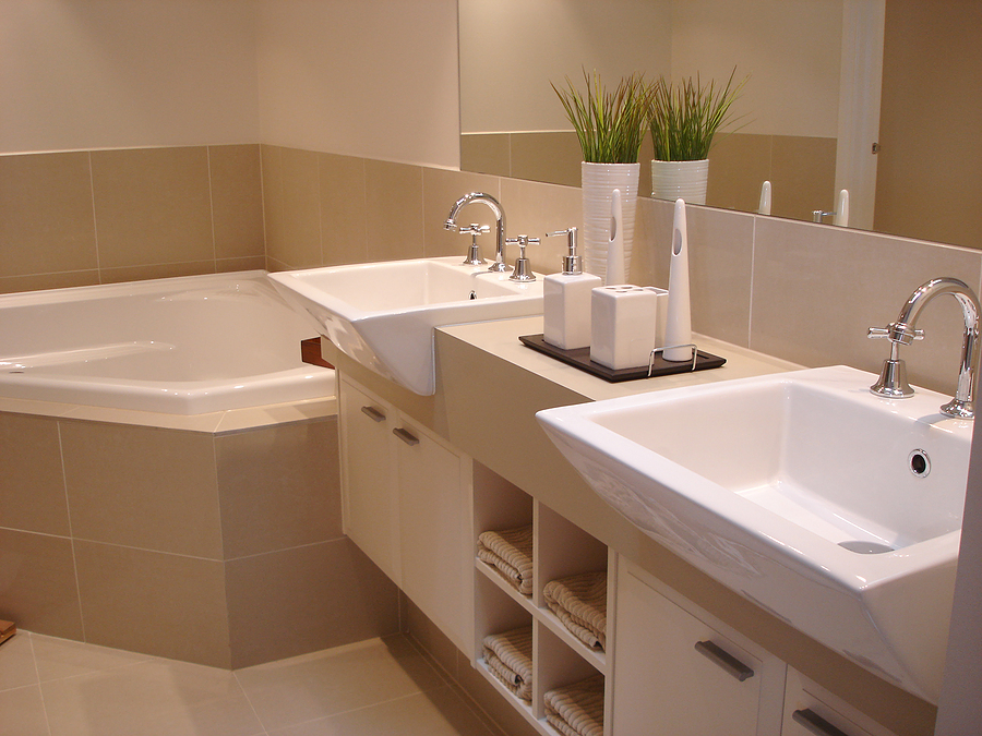 warm and minimalist bathroom design with small white corner tub with light  brown tub-wall