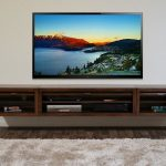 warm media center with floating media console made from solid wood an extra-size flat TV  soft and cozy white fury carpet dark-wood flooring