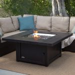 wood planks table with fire pit in the center L shape sofa with a lot of decortaive pillows for outdoor patio