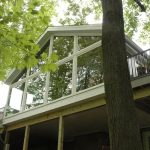 3 season room at second floor with full lenght glass windows  a home deck construction made from wood