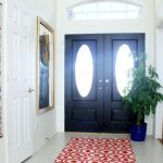 Joss and Main entryway rug a blue pot for decorative plant a black front door with oval glass panels a large decorative mirror with gold frame a simple crystal pendant lamp