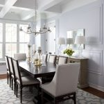 Joss and Main rug with beautiful patterns for classic dining room  a large dining table for eight dining chairs gold and crystal pendant chandelier a credenza with two table lamps and deorative mirrror
