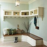 L shape corner bench made from wood for entryway with some decortaive pillows and a pair of boot shoes  L shape floating shelves with several under kits for hanging clothes and hand bags
