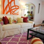 Large diagonal patterns Joss and Main carpet in pink and white colors a white sofa with colorful decorative pillows  a square glass surface table with additional panel on its bottom a black wood chair