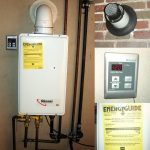 Rinnai tankless water heater installation with pipes and remote control wiring and alarm system on brick wall