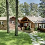 Two units of lake cabins in semi rustic style with trimmed glass door and glass windows a path with natural stone a beautiful lake in the back of cabins