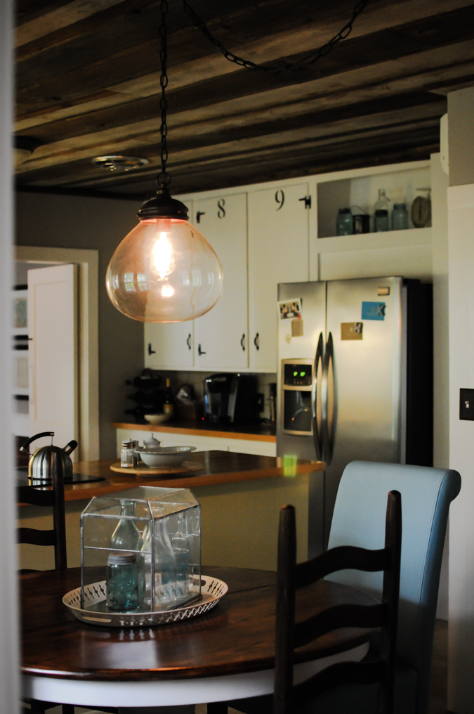 A Large Pendant Lighting Above Dining Furniture Black Wood Chairs And Soft Blue