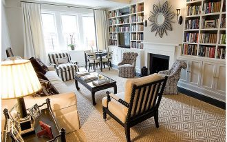 a light brown spool chair as the part of living room furniture extra large book shelves united with a fireplace building a decortive mirror a pair of wall lighting fixtures