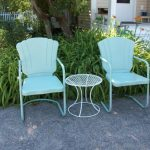 A Pair Of Metal Lawn Chairs With White Metal Whire Table In Round Shape