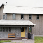 a pole barn house in pale color theme with soft yellow Dutch door as the front door