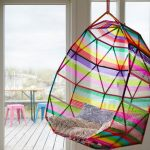 a rainbow hang chair with decorative pillow