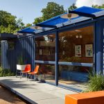 a shipping container house with large sliding glass door and glass window and porch  a pair of plastic patio chairs in orange