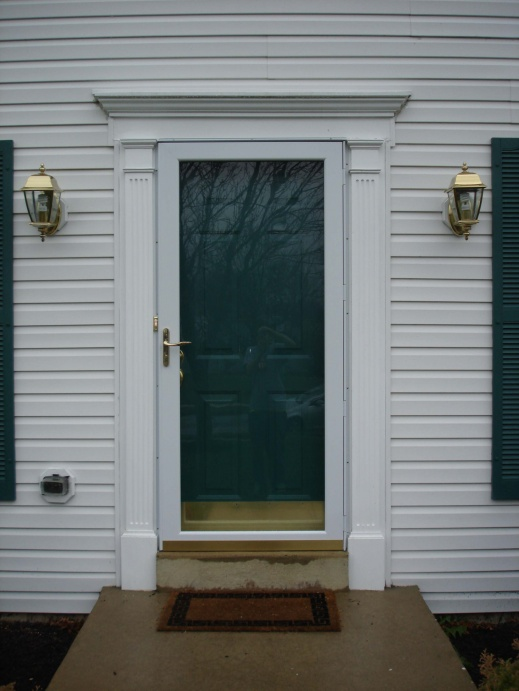 a storm door with two layers of panel and simple but beautiful door casing a pair