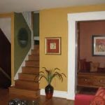 adorable color interior painting with green stair and yellow stucco wall feats with red sofa and wooden tread plus hallway bench