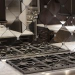 adorable diamong patterned antique mirror backsplash with cook top on white cabinetry with amazing lighting