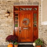 adorable furnished wooden front door design with double glass accent and christmas decoration beneath stone brick walland wooden ceiling design with pumpkins
